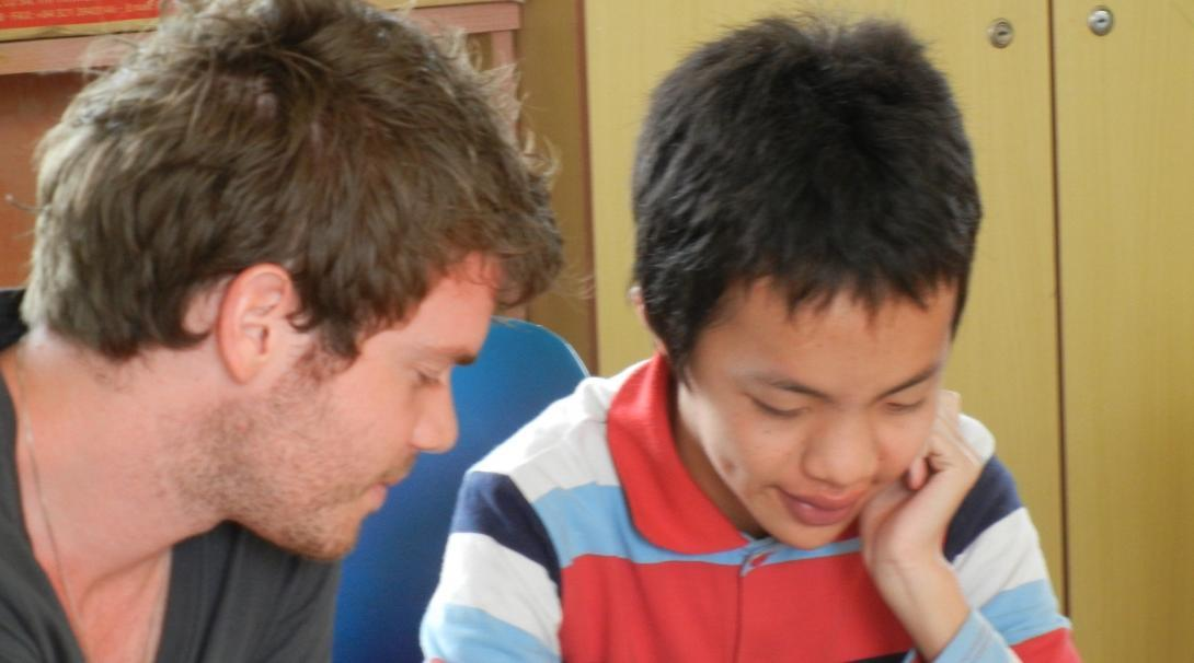 Pictured is a young intern from Projects Abroad teaching a child how to read as part of his speech therapy internship in Vietnam.